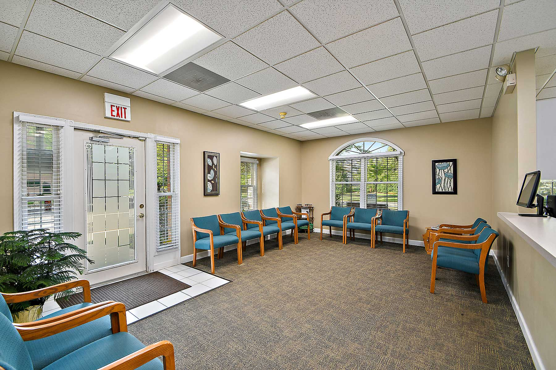 Orthodontic patient waiting room at Sonneveld Orthodontics. A large, beige-walled room with rows of teal chairs surrounding each side of the room. Front door is located on the left hand side of the image.