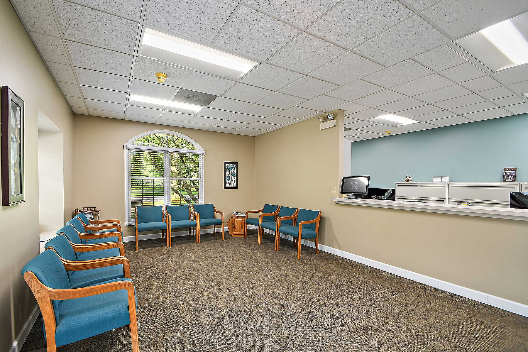 Orthodontic patient waiting room at Sonneveld Orthodontics. Orthodontic reception desk is located on the right hand side of the image, teal chairs are on each side of the walls.