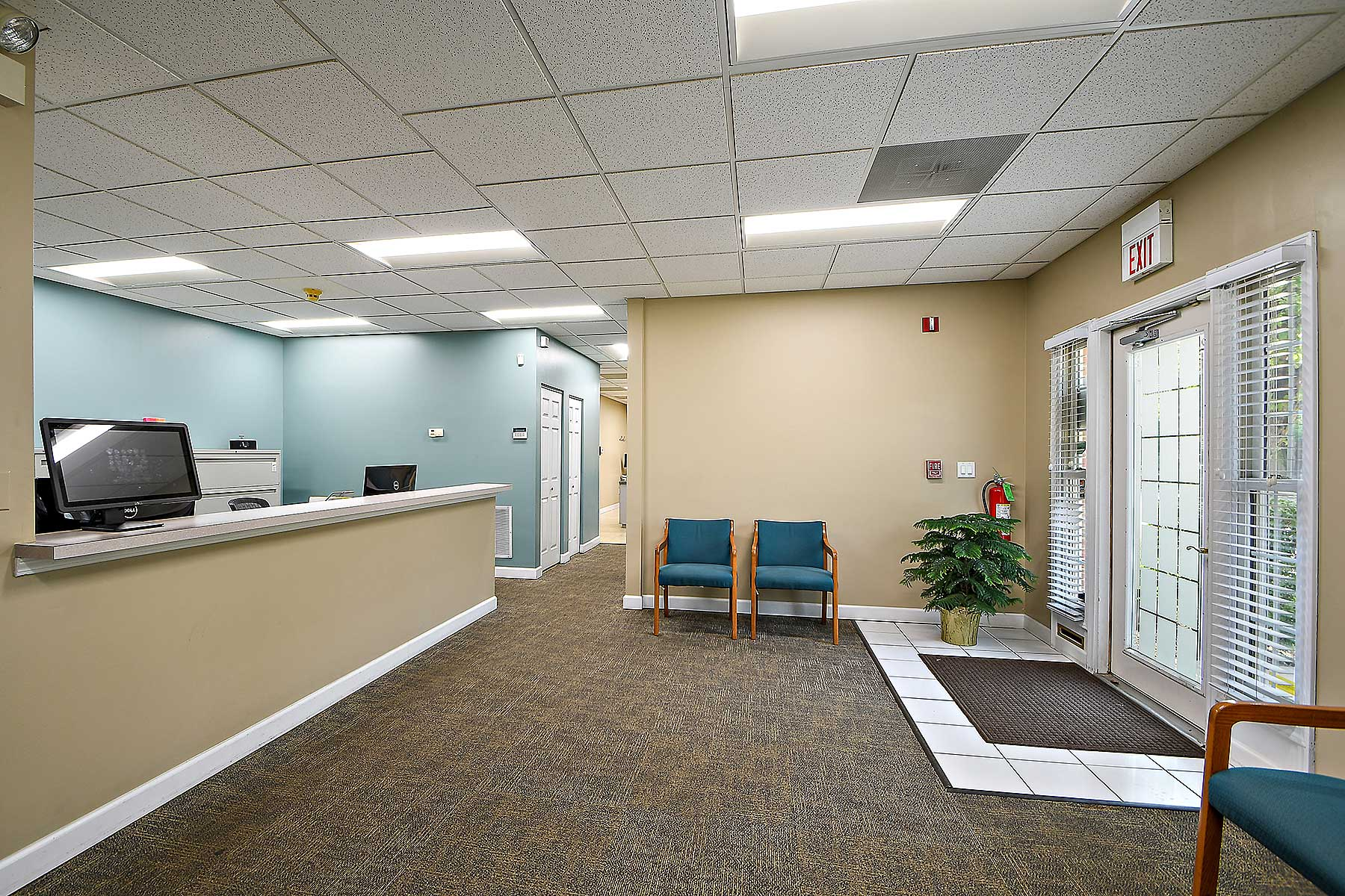 Orthodontic patient waiting room at Sonneveld Orthodontics. Orthodontic reception desk is located on the left hand side of the image, teal chairs are on each side of the walls.