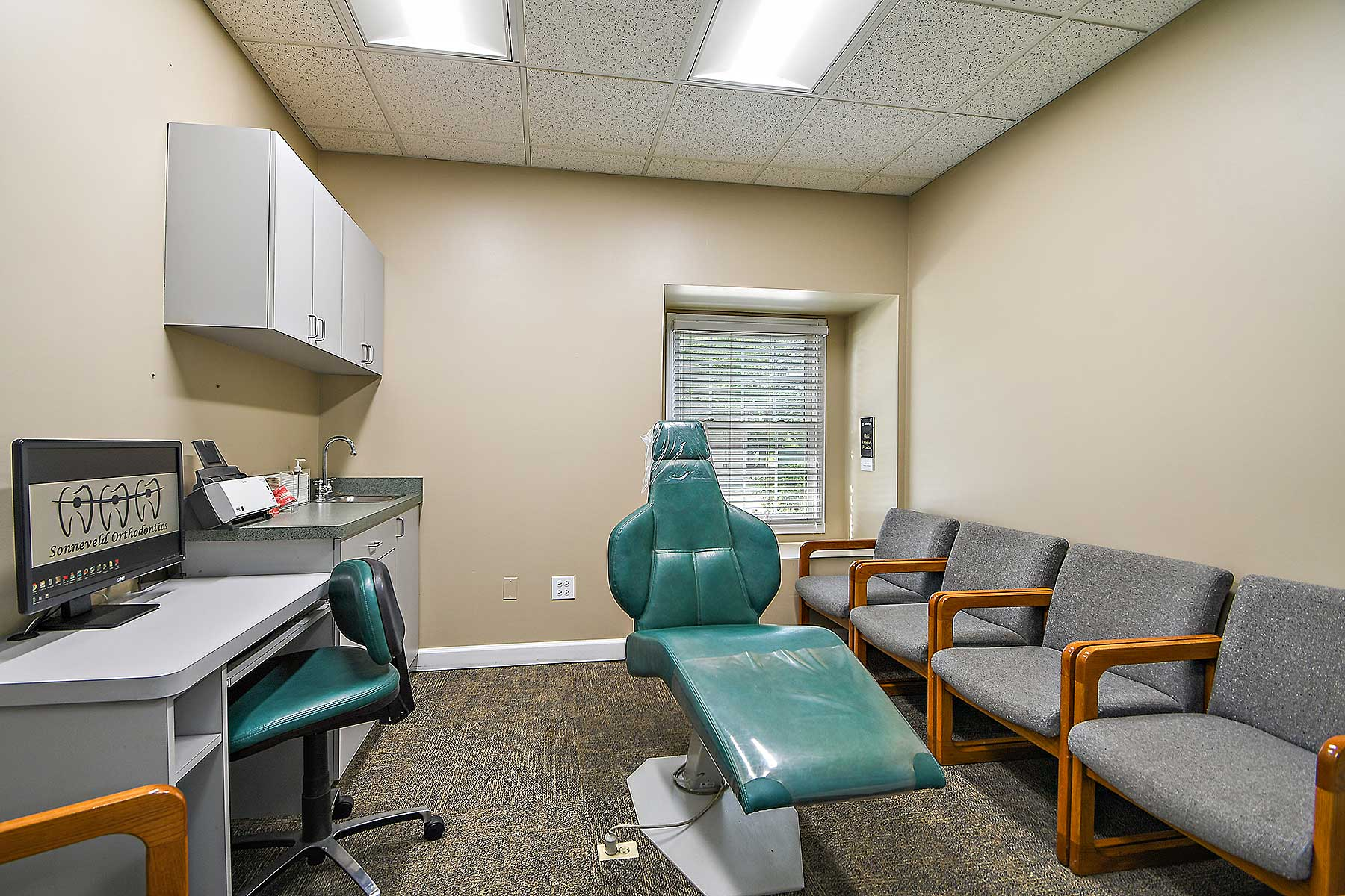 Teal colored orthodontic treatment chair is in the middle of the room, with beige walls and grey chairs along the right wall. A chair is located on the left side of the room at a desk with a computer that has the Sonneveld Orthodontics logo displayed.