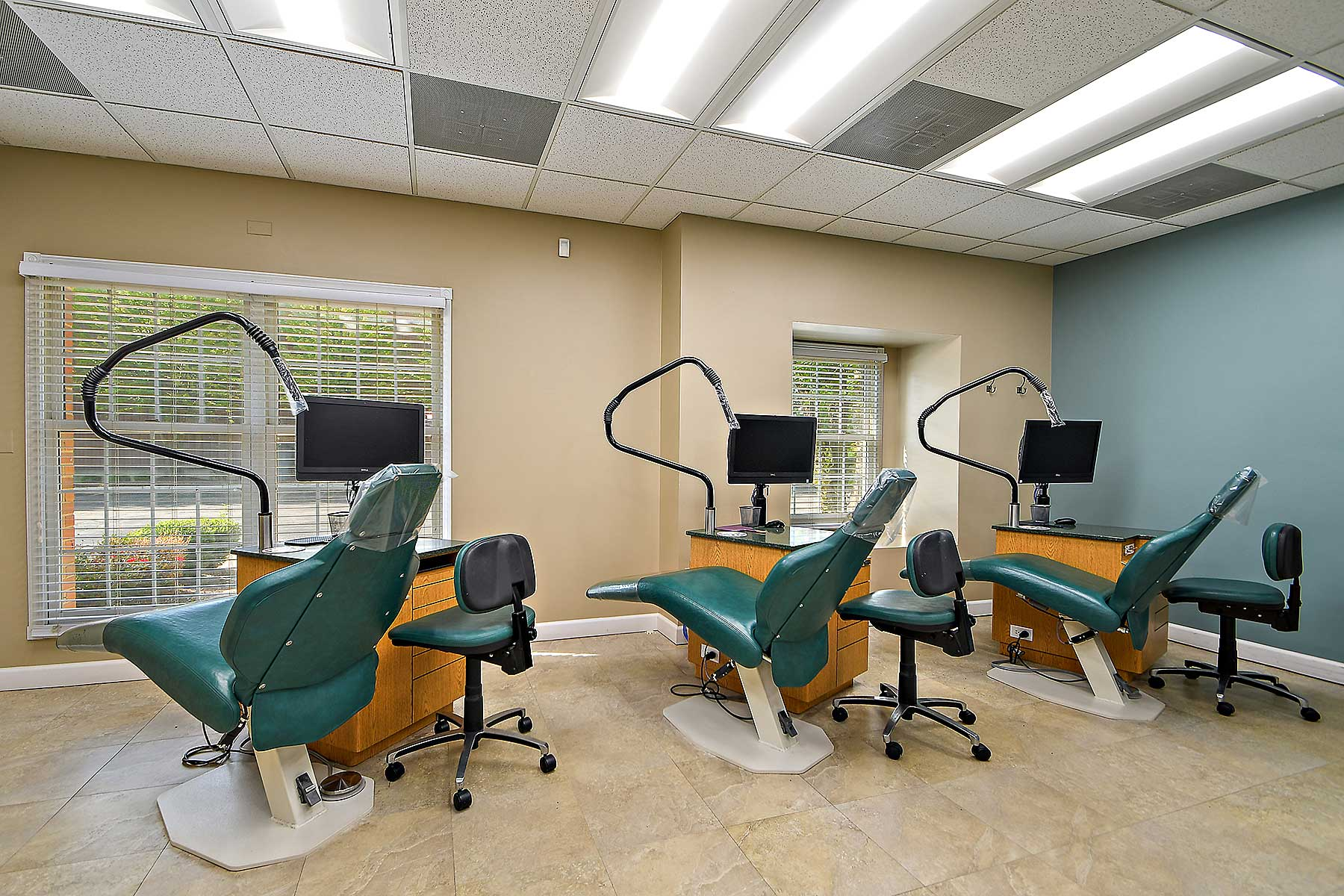 A large orthodontic patient room with three orthodontic treatment chairs lined up across the middle of the room. Each treatment chair has a doctor's station next to it, with a chair and computer.